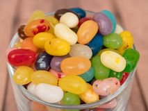 Jelly Beans in  jar. Close up of multicoloured jelly beans in a glass on a wooden background Stock Images