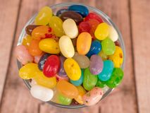 Jelly Beans in a jar. Close up of multicoloured jelly beans in a glass on a wooden background Royalty Free Stock Photos