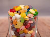 Jelly Beans in  jar. Multicoloured jelly beans in a glass on a wooden background Royalty Free Stock Photo