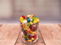 Jelly Beans in a jar. Multicoloured jelly beans in a glass on a wooden background Stock Images
