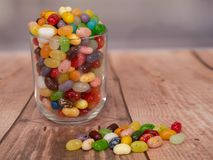 Jelly Beans in  jar. Multicoloured jelly beans in a glass on a wooden background, with some spilled on the surface Stock Photos