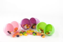 Jelly Beans and Plastic Eggs. Colorful jelly beans spill from plastic Easter eggs; room for copy on top Royalty Free Stock Photos