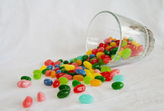 Jelly Beans spill from short glass Stock Photo
