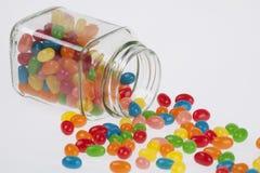 Jelly Beans-suikergoed van glaskruik wordt gemorst op witte backg die stock afbeelding