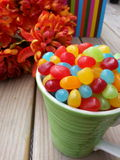 Jelly beans in a teacup with flowers and a book in the background. Multi-colored jelly beans in a teacup with flowers and a book in the background royalty free stock photography