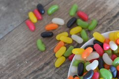 Jelly beans on a wooden backgroud. Jelly bean candy waiting to be eaten on a wooden backgroud stock photography