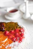 Jelly cake with tea. Strawberry, mango, orange jelly piece cake in table with tea Royalty Free Stock Images
