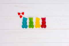Jelly candies in the form of a multicolored gummy bears with hea. Rts on wooden white table Stock Images