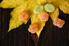 Jelly candy and autumn leaves on the wooden background. Top view.  Royalty Free Stock Images