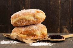 Jelly donuts with spoon of jam against dark wood Royalty Free Stock Photos