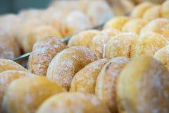 Jelly Filled Doughnut Cruller con Sugar Powdered Coating Bu?uelo relleno atasco sin agujero en la exhibici?n de la tienda de deli imagenes de archivo