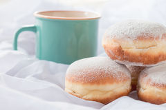 Jelly filled doughnuts and a coffee mug. In white sheets on a bed Royalty Free Stock Photography