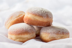 Jelly filled doughnuts with powdered sugar. On a bed with white sheets royalty free stock photo