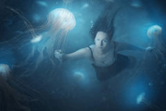 Jelly fish. A woman swimming in the deep ocean with jelly fish Royalty Free Stock Photo
