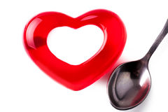 Jelly in the form of heart with a spoon. On a light background royalty free stock photography