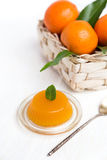 Jelly and fresh orange mandarins with leafs in basket Stock Photo