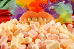 Caries. sweet denture. Dental prosthetics denture and little marshmallows on a colourful background. royalty free stock photos