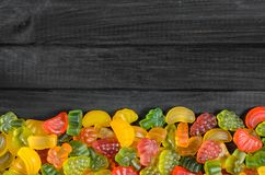 Jelly and marmalade candies on a wooden background stock image