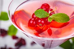 Jelly with red currant in martini glass on wooden background. Jelly with red currant  in martini glass on wooden background. Close up royalty free stock photo