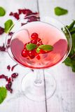 Jelly with red currant in martini glass on wooden background. Close up stock image