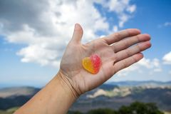 Jelly sweet candy heart on outstretched palm. Against the sky Stock Images