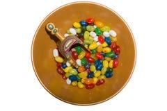 Jellybeans coloridos y cucharada de madera en cuenco Imagenes de archivo