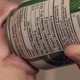 Jemand, das eine Dose mit den Ernährungsinformationen als der Fokus trinkt lizenzfreie stockfotografie