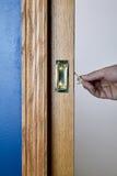 Jemand, das einen kleinen Metallhebel in der Tür anhebt Lizenzfreie Stockfotos