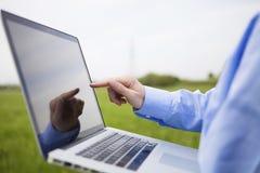 Jemand, das mit einem Laptop arbeitet Stockbild