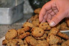 Jemand, das Schokolade Chip Cookies auf Platte nimmt Stockbild
