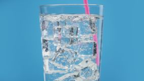 Jemand Getränk des kalten Wassers der Mischung mit funkelndem blauem Hintergrund des Sodas des Trinkhalms stock footage