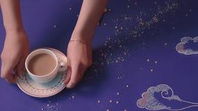 Jemand nimmt von einer Tabelle, die in Form eines n?chtlichen Himmels, ein Becher Kaffee, eine Nahaufnahme gemacht wird stock footage