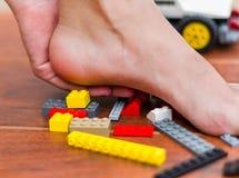 Jemand treten auf legos für Kinder, verschiedene farbige Blöcke Schmerz in der Ferse Stockbild