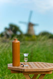 Jenever the national drink in Holland (EU). A bottle and a glass of jenever in front of a typical Dutch landscape Stock Photo