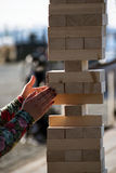 Jenga, girl`s hands try to pull out a wooden block, without tipp. Ing the tower, group game of physical skill with big blocks for outdoors, vertical stock photo