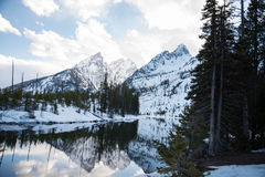 Jenny Lake. The scenery of Jenny Lake is partly covered with snow with pine forest and snowy mountains Royalty Free Stock Images