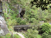 Jenolan Caves Bridge with Nettle Cave. View to the Jenolan Caves Bridge and the arch of the Devils Coach House Cave (Blue Mountains, Australia) with a Stock Image