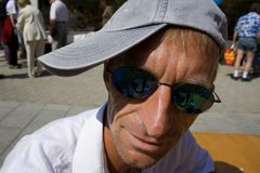 Jens close. Close up of man with sun glasses and a cap sideways Royalty Free Stock Photography