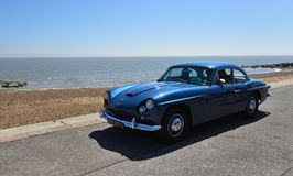 Jensen Motor Car azul clássico que está sendo conduzido ao longo do passeio da frente marítima imagens de stock royalty free