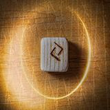Jera. Handmade scandinavian wooden runes on a wooden vintage background in a circle of light. Concept of fortune stock photography