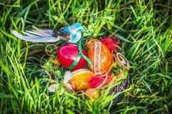 Jerarquía de Pascua con el adornamiento de los huevos y del pájaro azul en hierba del jardín Imagen de archivo