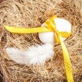 Jerarquía de Pascua con el huevo, la cinta amarilla y la pluma blanca en de madera Imagenes de archivo