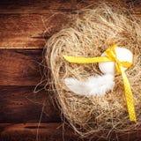 Jerarquía de Pascua con el huevo, la cinta amarilla y la pluma blanca en de madera Foto de archivo