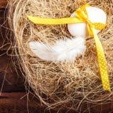 Jerarquía de Pascua con el huevo, la cinta amarilla y la pluma blanca en de madera Imágenes de archivo libres de regalías