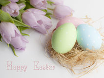 Jerarquía de Pascua con tres huevos y tulipanes del bouqet imagenes de archivo