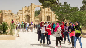 JERASH, JORDAN - APRIL 25, 2016:  Teens at the gate of Jerash. Happy young woman on girl`s day at the gate of Jerash Jordan Royalty Free Stock Photography