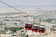Jericho. Cable way with tourists are going from the town to the top of the mount of  Temptation, with the town and desert in the background, , Palestine, Israel Stock Photos