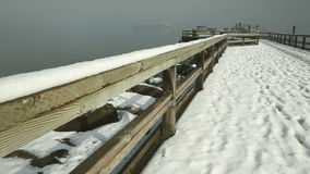 Jericho Pier, Winter, Vancouver, Canada. A dolly shot at Vancouver's Jericho Beach pier on English Bay after a winter snowfall.  The Vancouver skyline is stock video