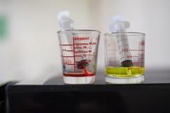 jeringuilla con el jarabe de la medicina en una medición de cristal farmacéutica Foto de archivo libre de regalías