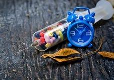 Jeringuilla con las píldoras y el reloj Foto de archivo